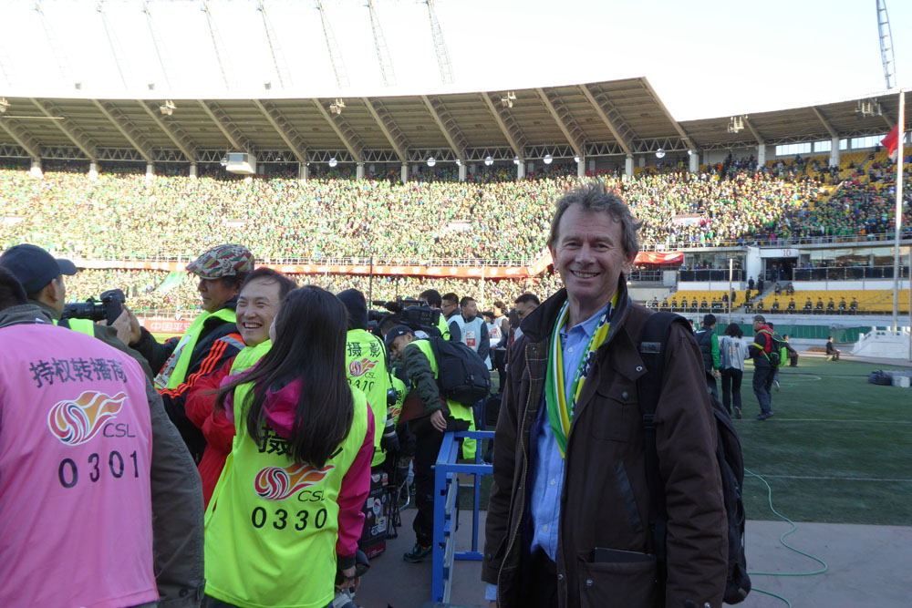 Michael Wood enjoys a pitch side view of the football match between Guo'an and Jianye in Beijing.